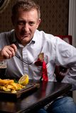 Fabulous at any age. Portrait of fashionable 50-year-old man in stylish siut posing at restaurant. Trendy haircut. Glossy grey hair. Charismatic man dining at stock photo