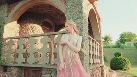 Fabulous blonde heroine in a wonderful pink light dress with a neat hairdo poses at the wall, holds gently with hand. Fabulous blonde heroine in a wonderful pink stock video