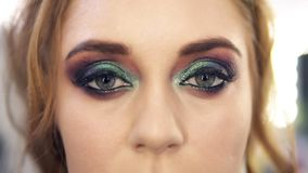 Fabulous bright haired woman with beautiful green eyes makeup opens her eyes. Front view stock footage
