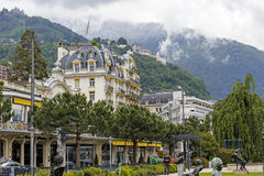Fabulous building and hills in Montreux. MONTREUX, SWITZERLAND - MAY 26, 2013: Fabulous building with yellow awnings and the hills on which in the distance you Stock Photography