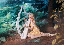 Fabulous forest elf sits under tree and plays on white harp, girl with long blond hair braided in long yellow dress royalty free stock photography