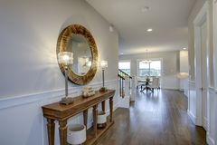 Fabulous foyer features a wood console table. Fabulous foyer features beige colored walls adorned with board and batten and furnished with a wood console table Royalty Free Stock Image