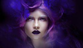 Fabulous girl with blue hair. Portrait in a wreath of roses, surrounded by the glare  fireflies Royalty Free Stock Images