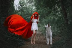 Fabulous girl with dark hair in short light white dress covers her head with hood of long bright red flying fluttering stock images