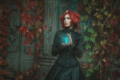 Fabulous girl with an hourglass. Fabulous girl with red hair, she is holding an hourglass. At the door of the castle Royalty Free Stock Image