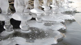 Fabulous ice columns. The columns were created under the ice on the river bank Głuszynka , thanks to the gradual lowering of the water level . Flowing river and Royalty Free Stock Photos
