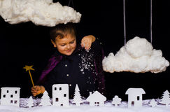 Fabulous kid throws the snow over the city on Christmas. Cute kid magician throws the snow through the clouds of the city at night on new year Stock Image