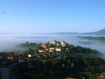 Fabulous landscape of the foggy morning in Tuscany. Stock Photos