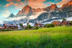 Fabulous mountain resort in the Dolomites, colorful spring flowers with high misty mountains and cute wooden houses at sunset, San stock photo