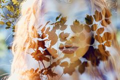 Fabulous portrait of a red-haired girl in nature with double exposure and glare. Beautiful redhead girl with long hair in forest royalty free stock photography
