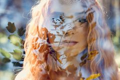 Fabulous portrait of a red-haired girl in nature with double exposure and glare. Beautiful redhead girl with long hair in forest stock photo