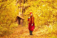 Fabulous redhead woman with long curly hair in red coat on autumn background. Girl on fabulous background of forest with orange au Stock Photos