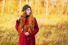 Fabulous redhead woman with long curly hair in red coat on blurred autumn background. Girl on fabulous background of forest with o Royalty Free Stock Photo