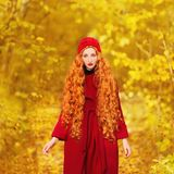 Fabulous redhead woman with long curly hair in red coat on blurred autumn background. Girl on fabulous background of forest with o Royalty Free Stock Photos