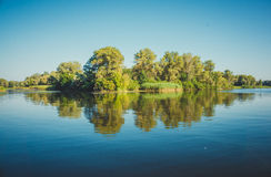 Fabulous reflection river island in serene surface of the water. Ukraine, the Dnieper river, vicinities of Kremenchuk Royalty Free Stock Photo