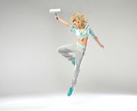 Fabulous shapely girl jumping with paint roller Royalty Free Stock Photos