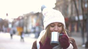 Fabulous smile. Girl stands on the Arbat, wind blows in the face. She drinks hot drink. She looks great with her fabulous smile. Winter stock video footage