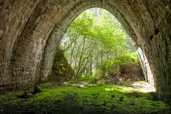 Fabulous stone tunnel with greenery, trees and moss, beautifully lit sun rays stock photography