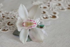 White orchid boutonniere small bouquet for buttonhole used for groom and wedding guests positioned on a white cloth Stock Photos