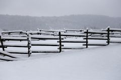Fresh snow filled corral fences at rural winter snowy horse farm Royalty Free Stock Image