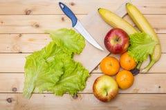 Faca, banana, maçãs, folhas da salada, tangerina e uma placa de madeira do corte em um fundo de madeira Foto de Stock