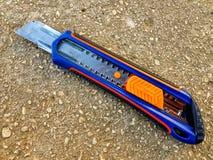 faca colorida do cortador isolada em uma superfície cobbled imagens de stock royalty free