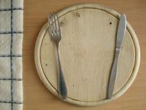Faca com uma forquilha em uma placa de madeira Placa de desbastamento com dispositivos de cozinha Um guardanapo quadriculado na t Imagem de Stock
