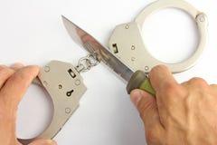 A faca corta a corrente das algemas Foto de Stock