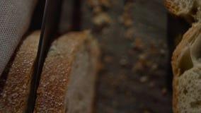 A faca corta o pão e as migalhas voam para baixo vídeos de arquivo