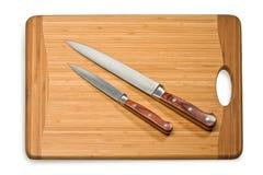 Faca de cozinha em uma placa de corte Imagens de Stock