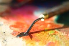 Faca de paleta suja após o trabalho nas mentiras de pintura em uma paleta de madeira imagem de stock