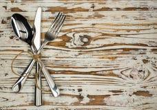 Faca e colher cruzadas de tabela da forquilha em placas de madeira velhas Fotografia de Stock Royalty Free