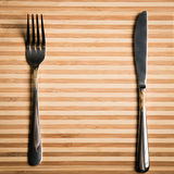 A faca e a forquilha ajustaram-se em uma placa de madeira Placa para homens de um restaurante Foto de Stock