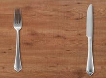 Faca e forquilha de tabela na madeira Fotografia de Stock Royalty Free