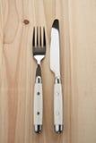 Faca e forquilha na tabela de madeira Fotografia de Stock Royalty Free