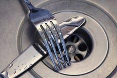 Faca e forquilha no dissipador de cozinha Imagem de Stock