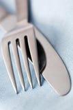 Faca e forquilha no linho azul Fotografia de Stock