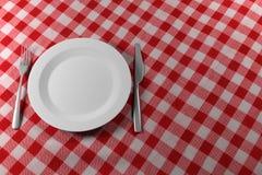 Faca e placa da forquilha em um pano de tabela vermelho Fotografia de Stock