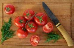Faca e ramo dos tomates em uma placa de desbastamento Imagens de Stock Royalty Free