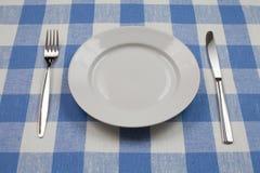Faca, placa branca e forquilha no tablecloth azul fotografia de stock