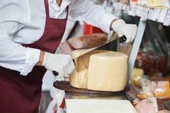Faca segurada dobro de Slicing Cheese With do vendedor foto de stock