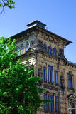 Facade. Of strictly building in a stone city against the dark blue sky and a green tree Stock Images