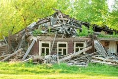 Facade of the abandoned destroyed wooden house with three windows with broken glass royalty free stock photography