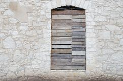 Facade of an abandoned old stone limestone house with boarded up royalty free stock photography