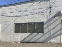 Facade of abandoned white washed building from outside with shadows and blue sky on a sunny day with copy space. Stock photo royalty free stock photography