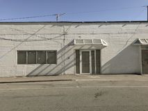 Facade of abandoned white washed building from outside with shadows and blue sky on a sunny day with copy space. Stock photo stock photos