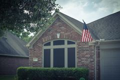 Facade of American home proudly displaying flag. Front porch of typical one story house proudly displaying American flag. Vintage tone Royalty Free Stock Photo