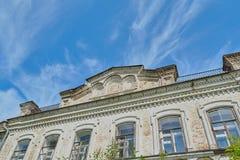 Symmetrical facade of an ancient building. Facade of an ancient building from a brick against the blue sky a Stock Image