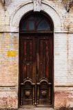 The facade of an ancient building with an old double-leafed brown wooden door decorated with voluminous carved patterns. Of wood in an archway of whitewashed stock images
