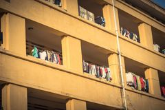 Facade of apartment and dormitory sun drying hanging clothes lin. Close-up of university dorm with sun drying hanging clothes line in dense of apartments in Stock Photo